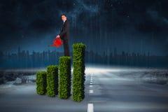 Imagen compuesta del hombre de negocios que sostiene la regadera roja Imagen de archivo libre de regalías