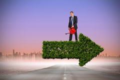 Imagen compuesta del hombre de negocios que sostiene la regadera roja Foto de archivo