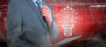 Imagen compuesta del hombre de negocios que sostiene la tableta digital Imágenes de archivo libres de regalías