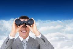 Imagen compuesta del hombre de negocios que sostiene los prismáticos Imágenes de archivo libres de regalías