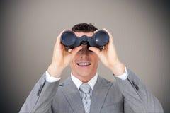 Imagen compuesta del hombre de negocios que sostiene los prismáticos Foto de archivo