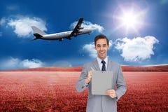 Imagen compuesta del hombre de negocios que sostiene un tablero Imagenes de archivo