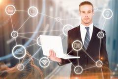 Imagen compuesta del hombre de negocios serio que presenta y que sostiene el ordenador portátil foto de archivo