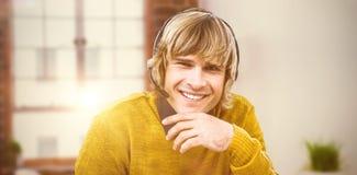 Imagen compuesta del hombre de negocios sonriente del inconformista usando las auriculares Imagen de archivo libre de regalías