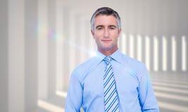Imagen compuesta del hombre de negocios sonriente en traje con las manos en la presentación del bolsillo Imagen de archivo