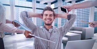 Imagen compuesta del hombre de negocios sonriente que es dado artículos imagen de archivo libre de regalías