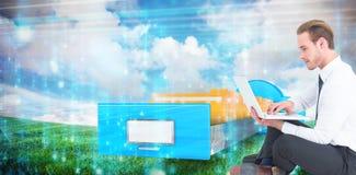 Imagen compuesta del hombre de negocios sonriente que se sienta en piso usando el ordenador portátil Imagen de archivo libre de regalías
