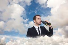 Imagen compuesta del hombre de negocios sorprendido que coloca y que sostiene los prismáticos Imágenes de archivo libres de regalías