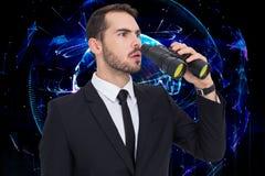Imagen compuesta del hombre de negocios sorprendido que coloca y que sostiene los prismáticos Foto de archivo libre de regalías