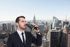 Imagen compuesta del hombre de negocios sorprendido que coloca y que sostiene los prismáticos Imagen de archivo libre de regalías
