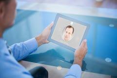 Imagen compuesta del hombre de negocios usando su tableta Imágenes de archivo libres de regalías