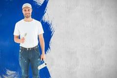 Imagen compuesta del hombre feliz que sostiene el rodillo y la brocha de pintura Foto de archivo libre de regalías