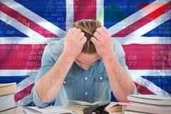 Imagen compuesta del hombre frustrado con la mano en pelo mientras que se sienta en el escritorio Fotografía de archivo