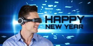 Imagen compuesta del hombre hermoso feliz con el simulador de la realidad virtual Fotos de archivo libres de regalías