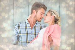 Imagen compuesta del hombre hermoso que coge y que abraza a su novia Fotos de archivo libres de regalías