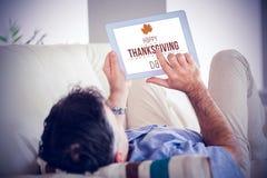 Imagen compuesta del hombre que pone en el sofá usando una PC de la tableta Fotografía de archivo