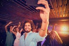Imagen compuesta del hombre que toma un selfie del teléfono móvil mientras que amigos que bailan en sala de baile Fotografía de archivo libre de regalías