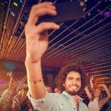 Imagen compuesta del hombre que toma un selfie del teléfono móvil mientras que amigos que bailan en sala de baile Imagenes de archivo