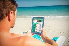 Imagen compuesta del hombre que usa la tableta digital en silla de cubierta en la playa Imagen de archivo libre de regalías