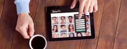 Imagen compuesta del hombre usando la tableta digital mientras que comiendo la taza de café foto de archivo libre de regalías