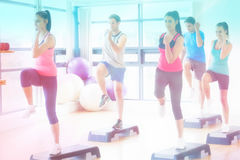 Imagen compuesta del instructor con la clase de la aptitud que realiza ejercicio de los aeróbicos del paso Imagen de archivo libre de regalías