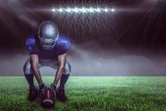 Imagen compuesta del jugador de fútbol americano en bola que se sostiene uniforme mientras que se agacha Fotos de archivo