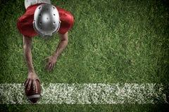 Imagen compuesta del jugador de fútbol americano que miente en frente con la bola Imágenes de archivo libres de regalías