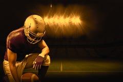 Imagen compuesta del jugador de fútbol americano que se arrodilla mientras que sostiene la bola Fotos de archivo libres de regalías