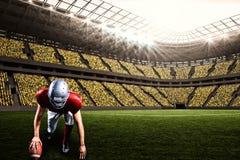 Imagen compuesta del jugador de fútbol americano que toma la posición mientras que sostiene la bola con 3d Imagenes de archivo