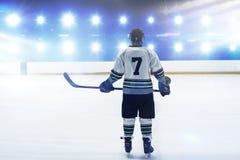Imagen compuesta del jugador de hockey con la situación del palillo de hockey en pista imagen de archivo