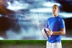 Imagen compuesta del jugador de los deportes que parece ausente mientras que sostiene la bola foto de archivo