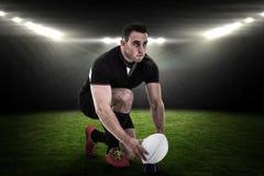 Imagen compuesta del jugador del rugbi que consigue lista para golpear la bola con el pie Fotos de archivo libres de regalías