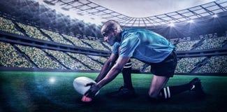 Imagen compuesta del jugador del rugbi que guarda la bola en el retroceso de la camiseta con el pie con 3d Imagenes de archivo