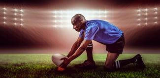Imagen compuesta del jugador del rugbi que guarda la bola en el retroceso de la camiseta y de 3d con el pie Imagen de archivo libre de regalías
