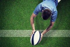 Imagen compuesta del jugador del rugbi que miente en frente con la bola Imagen de archivo