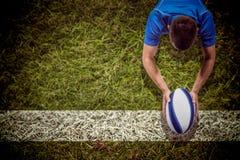 Imagen compuesta del jugador del rugbi que miente en frente con la bola Foto de archivo libre de regalías