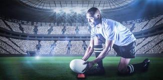 Imagen compuesta del jugador del rugbi que parece ausente mientras que guarda la bola en el retroceso de la camiseta con el pie c Fotografía de archivo