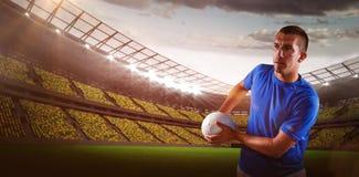Imagen compuesta del jugador del rugbi que parece ausente mientras que sostiene la bola fotografía de archivo