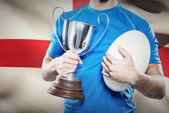 Imagen compuesta del jugador del rugbi que sostiene el trofeo y la bola Fotos de archivo libres de regalías