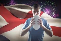 Imagen compuesta del jugador del rugbi que sostiene una bola de rugbi Fotos de archivo libres de regalías