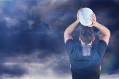 Imagen compuesta del jugador devuelto del rugbi que lanza una bola 3D Foto de archivo