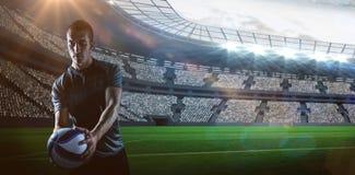 Imagen compuesta del jugador hermoso del rugbi que celebra la bola fotos de archivo libres de regalías