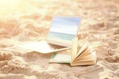 Imagen compuesta del libro y del ordenador portátil abiertos en la arena en la playa Fotografía de archivo libre de regalías