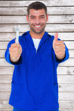 Imagen compuesta del mecánico sonriente que detiene a la llave inglesa mientras que gesticula los pulgares para arriba Fotografía de archivo libre de regalías