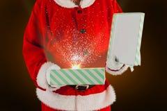 Imagen compuesta del midsection de la caja de regalo de la abertura de Papá Noel Imagen de archivo libre de regalías