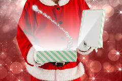 Imagen compuesta del midsection de la caja de regalo de la abertura de Papá Noel Foto de archivo