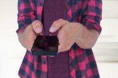 Imagen compuesta del midsection del hombre en casual usando el teléfono elegante Fotos de archivo libres de regalías