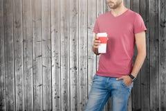 Imagen compuesta del midsection del modelo masculino que sostiene la taza disponible fotografía de archivo