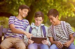 Imagen compuesta del muchacho con los amigos que usan la tableta digital en banco Imágenes de archivo libres de regalías