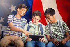 Imagen compuesta del muchacho con los amigos que usan la tableta digital en banco Fotos de archivo libres de regalías